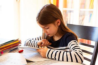 Girl doing homework with digital tablet - p300m2180360 by Larissa Veronesi