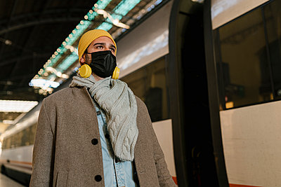 Man with protective face mask and headphones looking away while standing by train at station - p300m2251061 by Ezequiel Giménez