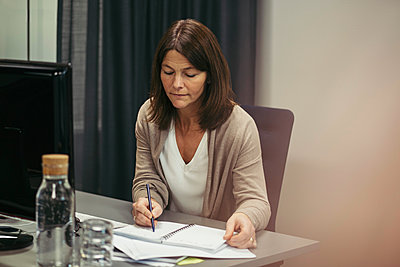 Businesswoman writing in diary while sitting at desk in office - p426m1468385 by Maskot