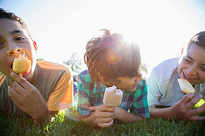 Hispanic boys laying in grass eating popsicles - p555m1232026 by Ronnie Kaufman/Larry Hirshowitz