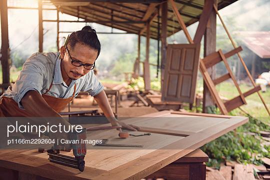Carpenters using circular saw in workshop - p1166m2292604 by Cavan Images