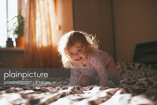 Happy toddler girl crawling on bed - p1642m2222257 by V-fokuse