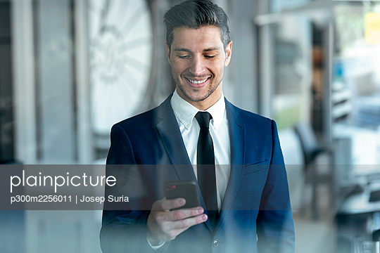 Smiling entrepreneur wearing suit using mobile phone while standing in office - p300m2256011 by Josep Suria