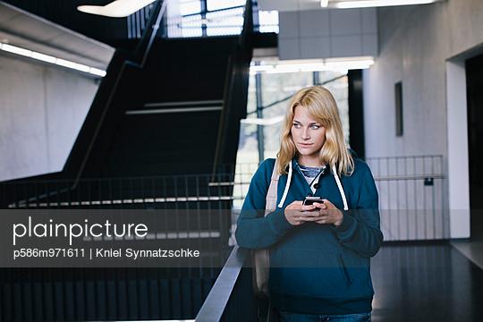 Blonde Studentin mit Handy im Treppenhaus - p586m971611 von Kniel Synnatzschke