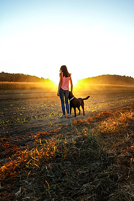 Teenage Girl and her Dog at sunset - p1019m1487238 by Stephen Carroll
