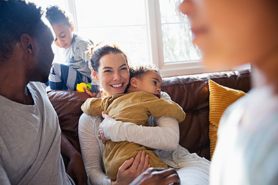Happy mother cuddling baby son, relaxing with family on living room sofa - p1023m2016688 by Sam Edwards
