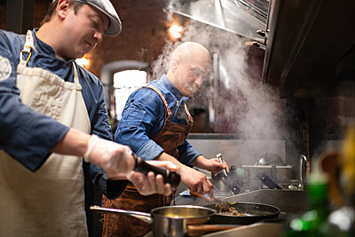 Male chefs cooking together in restaurant - p1166m2250624 by Cavan Images