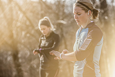 Caucasian runners checking fitness watches in forest - p555m1412830 by John Fedele