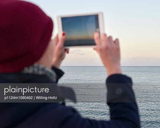 Frau fotografiert das Meer mit Ipad - p1124m1090462 von Willing-Holtz