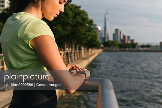 Half body image of woman checking smart watch while stopped for run - p1166m2292586 by Cavan Images