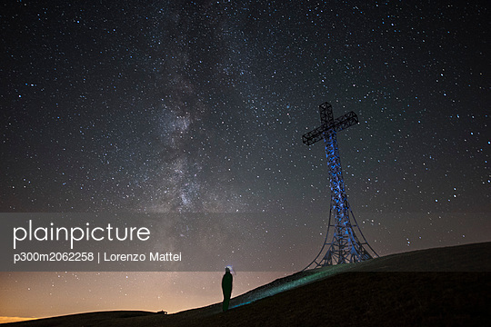 Italy, Marche, silhouette of man looking at summit cross on Monte Catria at night - p300m2062258 by Lorenzo Mattei