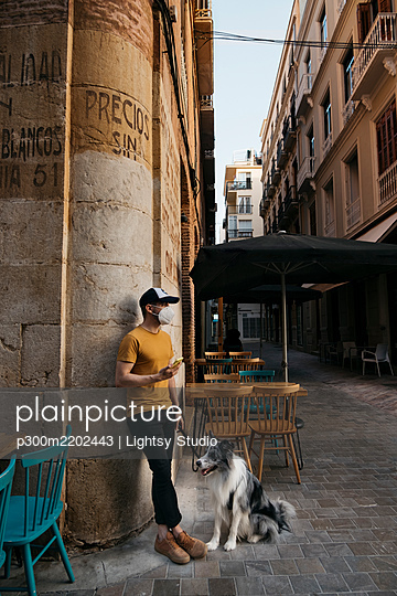 Man wearing protective mask waiting with his dog in the city - p300m2202443 by Lightsy Studio