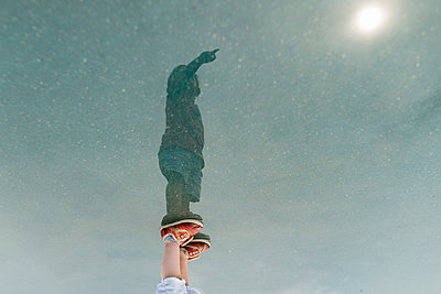 Reflection of boy with hand raised standing in puddle - p1166m1186109 by Cavan Images