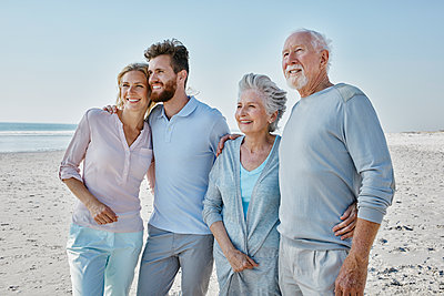 Smiling senior couple with adult children on the beach - p300m1450079 by Roger Richter