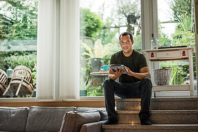 Portrait of smiling man at home sitting on stairs using tablet - p300m1505671 by Robijn Page