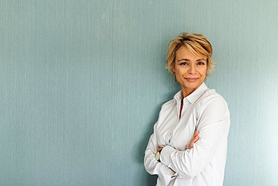 Portrait of confident mature woman standing at a wall - p300m2144795 by Valentina Barreto