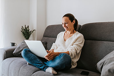 Smiling woman sitting cross-legged using laptop on sofa in living room - p300m2240190 by David Molina Grande