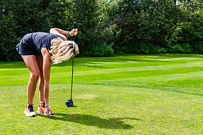 A female golfer places a golf ball on a tee while holding her driver; Edmonton, Alberta, Canada - p442m2019620 by LJM Photo