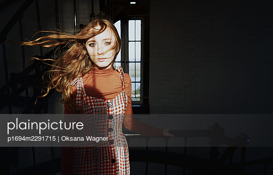 Beautiful red-haired young woman with wind-blown hair in a dark room looking at camera  - p1694m2291715 by Oksana Wagner