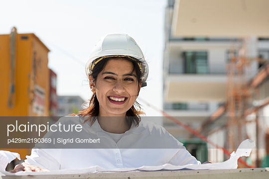 Female architect wearing white hard hat working on construction site, smiling at camera. - p429m2190369 by Sigrid Gombert