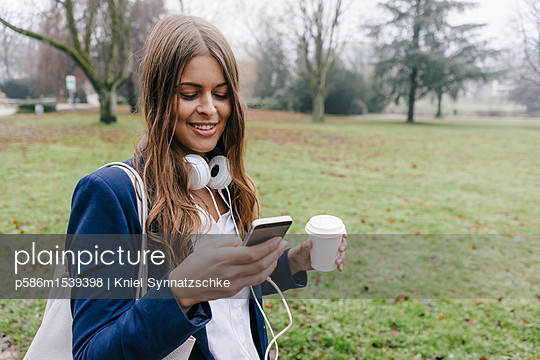 Young woman with smartphone and coffee to go - p586m1539398 by Kniel Synnatzschke