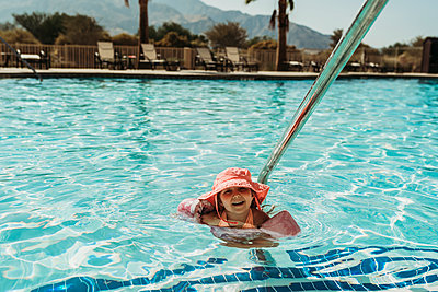Young preschool age girl swimming in pool on vacation in Palm Springs - p1166m2218181 by Cavan Images
