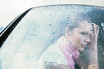 Womans face behind car windscreen in rain dreaming - p4020434 by Ramesh Amruth