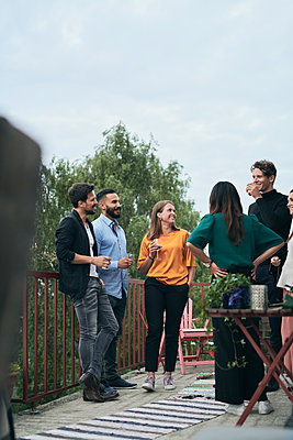 Happy friends talking while standing on terrace during social gathering - p426m2074514 by Maskot
