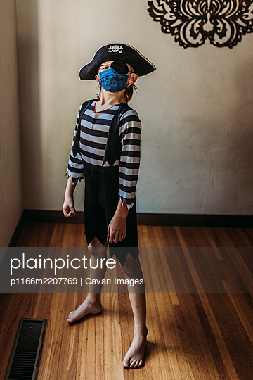 Full length of young boy dressed as pirate with face mask on - p1166m2207769 by Cavan Images
