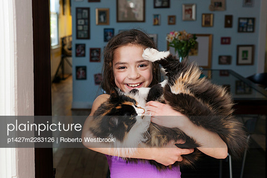 Girl holding pet cat - p1427m2283126 by Roberto Westbrook