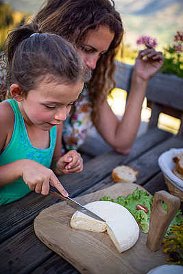 Frankreich, Girl cutting cheese - p1007m2219946 by Tilby Vattard