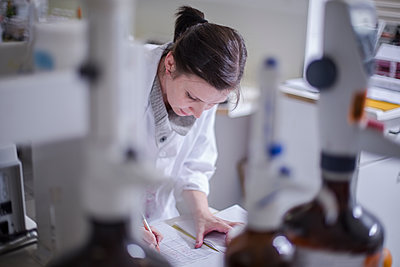 Woman taking notes in lab - p300m1175688 by zerocreatives