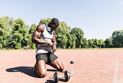Young athlete kneeling on sports field, checking smartwatch - p300m2005347 von Uwe Umstätter