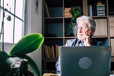 Contemplating senior businessman looking away while sitting with laptop at home - p300m2276619 by Simona Pilolla