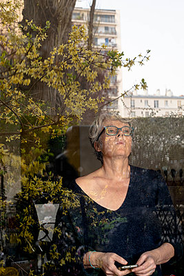 Grey-haired woman looking out of window - p445m2173646 by Marie Docher