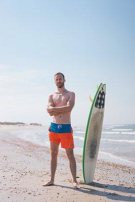 Mann mit Surfbrett am Strand - p586m1041261 von Kniel Synnatzschke