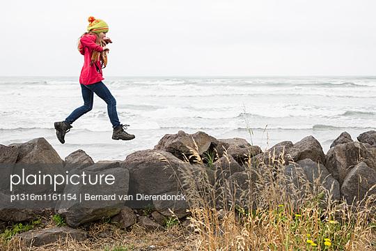 Ein Mädchen springt über Felsen, Sumner Beach, Christchurch, South Island, Neuseeland - p1316m1161154 von Bernard van Dierendonck