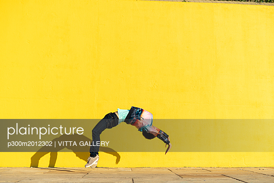 Acrobat jumping somersaults in front of yellow wall - p300m2012302 von VITTA GALLERY