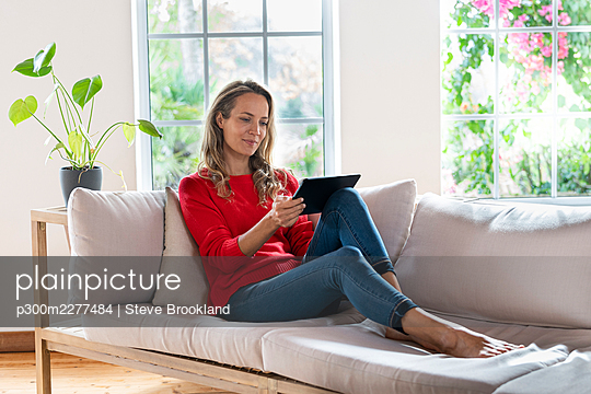 Blond woman with digital tablet sitting on sofa in living room - p300m2277484 by Steve Brookland