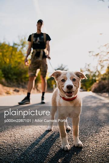 Boy walking his dog on a path in nature - p300m2287101 von Aitor Carrera Porté