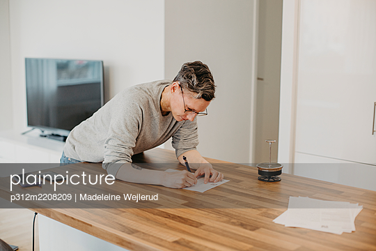 Woman writing on kitchen worktop - p312m2208209 by Madeleine Wejlerud