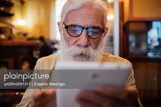 Senior businessman using digital tablet in cafe - p429m2091311 by Eugenio Marongiu