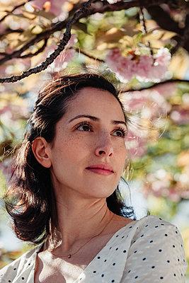 Portrait einer Frau inmitten von Kirschblüten - p045m2027642 von Jasmin Sander
