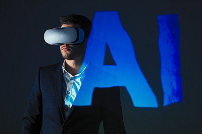 Double exposure businessman with virtual reality simulator glasses against AI text - p1023m2135713 by Paul Bradbury
