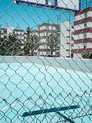 Blurred basketball court through ball stop fence - p1166m2129971 by Cavan Images