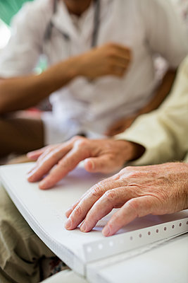 Blind senior man using braille to read in a retirement home - p1315m1186289 by Wavebreak