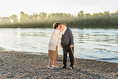 Happy senior couple kissing on the beach - p300m1460058 by Uwe Umstätter