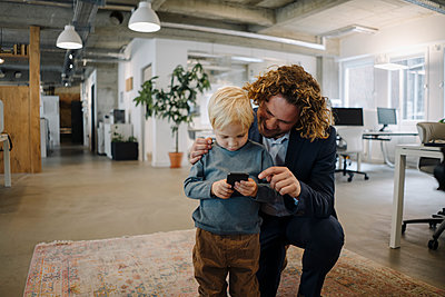 Businessman with son in office using cell phone - p300m2167332 by Kniel Synnatzschke
