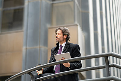 Thoughtful businessman looking away while holding digital tablet and coffee cup in front of railing - p300m2277206 by Jose Carlos Ichiro