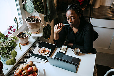 Young female entrepreneur sitting with laptop while working from home - p426m2284877 by Maskot
